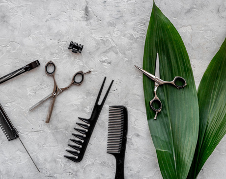 Beauty saloon. Haidressing tools on grey table background top view